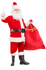 Santa Claus holding a bag full of gifts and giving a thumb up