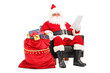 Santa Claus in armchair reading a letter next to a bag full of g