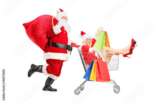Santa Claus pushing a woman with shopping bag in a push cart