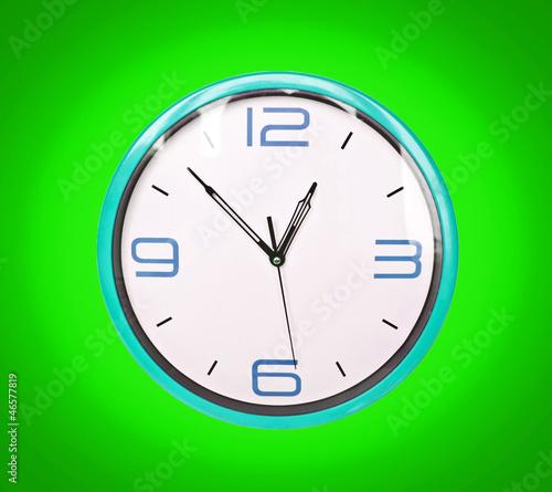 Leinwanddruck Bild Retro blue clock on green background