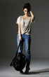 portrait of standing young woman jeans holding handbag posing