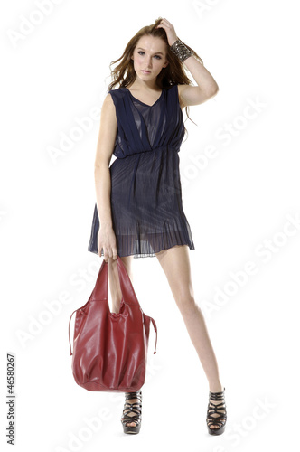 beautiful woman in hat with handbag posing