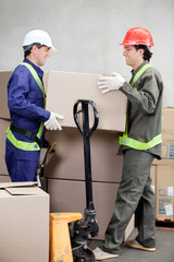 Foremen Lifting Cardboard Box At Warehouse
