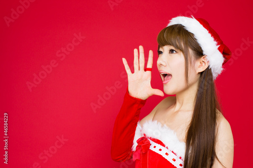 Beautiful asian woman in santa hat excited for Christmas on red