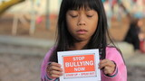 Sad Asian Girl Holds A Stop Bullying Sign