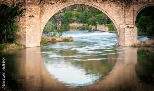 Bridge reflects in river of Toledo, Spain, Europe.