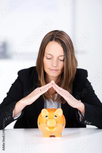 frau hält hände über sparschwein