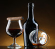 bottle and glasss of brandy and cigar on brown background