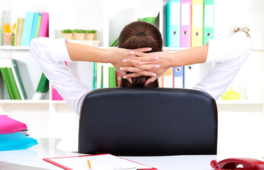Business woman relaxing in office with hands behind head