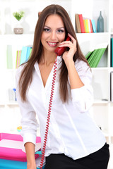 Young pretty business woman with phone working at office