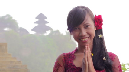 balinese girl saluting with both hand in uluwatu temple, bali