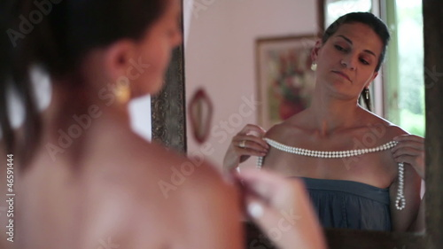 Beautiful woman trying on pearl necklace