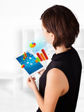 Young woman looking at modern tablet with colourful diagrams