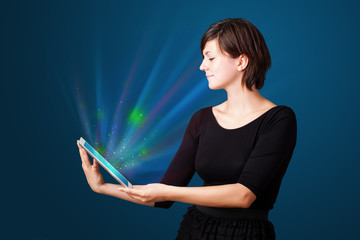Young woman looking at modern tablet with abstract lights