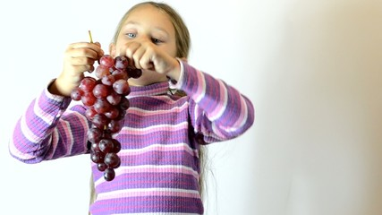 girl holding a bunch of grapes