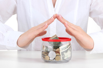 Woman hands with money in glass jar isolated on white