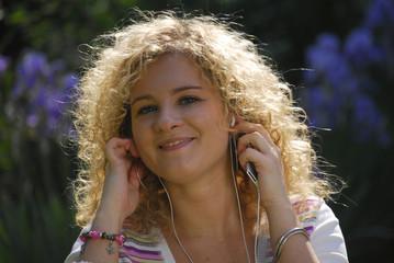 Mujer escuchando música, usando audífonos en un jardín.