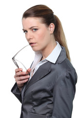 Businesswoman holding glasses with serious expression on face
