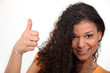 Woman with curly hair giving the thumb's up