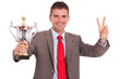 business man with trophy and victory sign