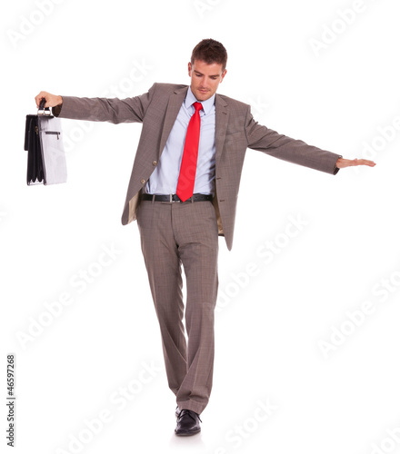 Business man with briefcase walk on wire