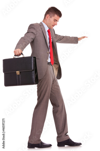 business man with briefcase balancing