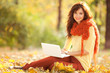 Cute woman with white laptop in the autumn park