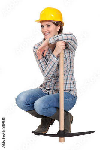 Woman kneeling by a pickax