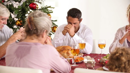 Family saying grace at the dinner table at christmas