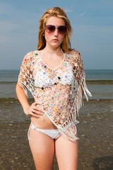 Pretty girl red long hair wearing white bikini on the beach.