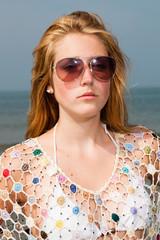 Pretty girl with red long hair wearing white bikini on the beach