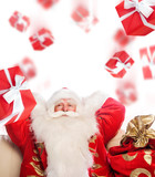 Santa Claus sitting with a sack indoor relaxing and Gift boxes f