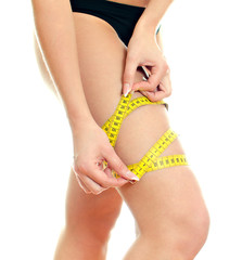 Slim female body with measure tape around leg.