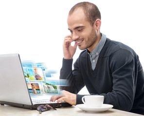 A young man sitting in front of a laptop and sharing photo and v