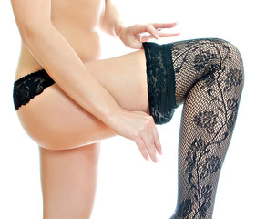 Young woman pulling on one stocking.