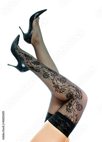 Sexy female legs in black stockings raised up. Isolated on white