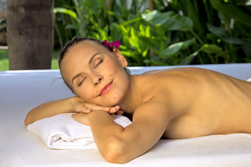 Woman with eyes closed, lying on a spa bed.