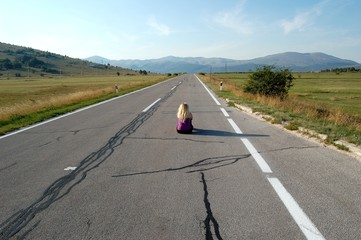 Girl sitting on an empty road