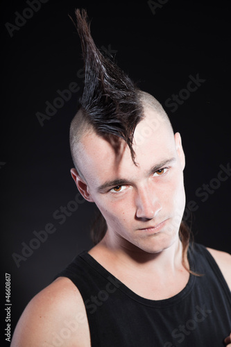 Punk rock man with mohawk haircut against black background.