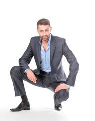 Portrait businessman sitting on his haunches