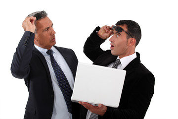 Amazed businessmen holding a laptop