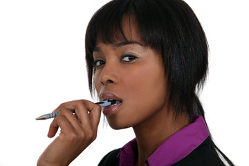 A pensive woman chewing on her pen