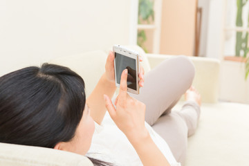 ソファーでスマートフォンを見る女性