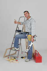 Carpenter stood by ladder giving the thumbs-up