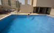 man swim in swimming pool at roof of apartment, bahrain