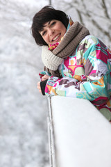 Woman leaning against a snow-covered ledge