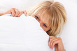 Attraktive Frau versteckt sich unter Bettdecke