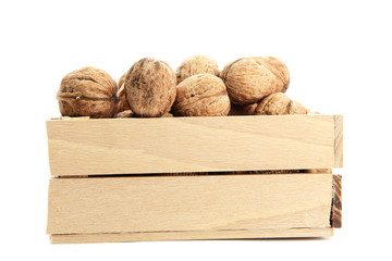 walnuts in woooden crate, isolated on white