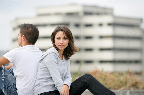 Young couple sitting back to back