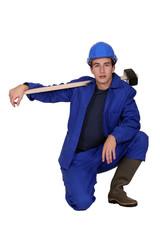 Man with sledge-hammer kneeling